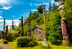 Native American Clan House and Totems. Ketchikan, AK, USA - May 24, 2016: Native American Totems and Clan Houses located at Totem Bight State Historic Site royalty free stock photo