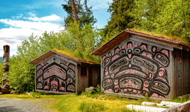 Native American Clan Houses. Ketchikan, AK, USA - May 24, 2016: Native American Totems and Clan Houses located at Totem Bight State Historic Site royalty free stock photography