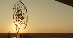 Native American dreamcatcher hanging in breeze at sunset.