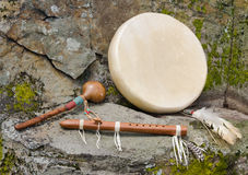 Native American Drum with Flute and Shaker.. Large, flat, Native American Drum with decorative feathers, and a Hand Carved Flute, and Shaker against a natural Royalty Free Stock Photos