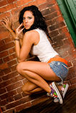 Native American Fashion model. Brunette native american female fashion model in cut-off shorts and white tank top against a brick wall in the studio stock images