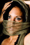 Native american female fashion model. Brunette native american female fashion model with see through scarf over her face shot against black stock image