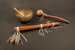 Native American Flute and Shaker, and Tibetan Singing Bowl. Native American Flute with Feathers and Beaded Shaker with Tibetan Singing Bowl and Ringing Stick Stock Photo