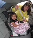 Native American girl in a child safety seat. Natuve American woman placing her daughter in a child safety seat and fastening her seat belt Stock Images