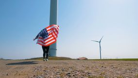 Native American girl with a flag near a giant windmill in a field in slow motion. Native American girl with flag with stars and stripes near giant windmills in stock footage