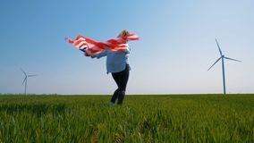 Native American girl with a flag near a giant windmill in a field in slow motion. Native American girl with flag with stars and stripes near giant windmills in stock video footage