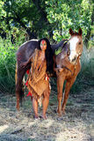 Native American and Her Horse. A Native American woman stands next to her horse stock photo