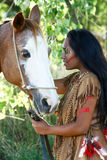 Native American and Her Horse. A Native American woman stands next to her horse royalty free stock images