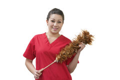 Native American house cleaner holding feather duster over white background Stock Photos