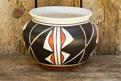Native American Indian pottery on wood shelf. Contemporary Native American Indian pot using ancient Indian design. Pot is sitting on an old wood shelf Royalty Free Stock Image