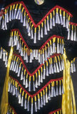 Native American Indian powwow. Dancer with bells, back of costume Stock Photos