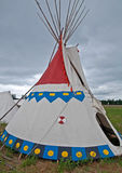 Native American Indian TeePee. This is a traditional Native American Indian teepee, set up in a vertical image against, stormy cloudy skies. The doorway is ready stock photo