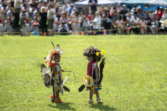 Native American kids. Preparing for the smoke dance at Kahnawake POW WOW while wearing their tribe`s costumes Stock Photos