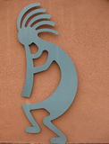 Native American Kokopelli. Kokopelli is a native american symbol for their god of fertility and music. He is a teal colored flute player against an adobe Stock Photo