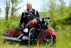 Native American man with Indian Motorcycle. Native American man enjoying the country with his Indian motorcycle Royalty Free Stock Image