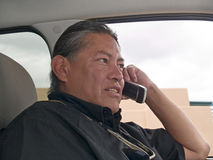 Native American man talking on cell phone. In his parked car Stock Photos