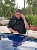 Native American man talking on cell phone. Native American man doing business by the hood of his car Royalty Free Stock Image