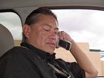Native American man talking on cell phone. In his parked car Stock Photography