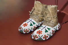 Native American Moccasins. A pair of Native American moccasins sitting on a red floor Royalty Free Stock Photography