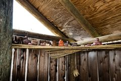 Native American pottery, pipes, and other items rest on a bundled reed shelf inside a Summer House. Native American pottery, smoking pipes, cups and other items stock images