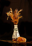Native American still life. Photo of Native American vase with dried native vegetation, and arrow head on black glass with black background stock images
