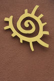 Native American Sun Symbol. A yellow Native American Sun Symbol against a stucco wall Royalty Free Stock Images