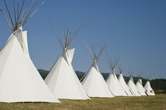 Native American Teepee Village of Eight. Eight Native American Teepees on grass in front of wooded hills Stock Images