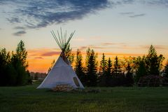 Native American Tepees on the Prairies at Sunset. An array of indigenous tee-pees on the prairie grass set up for a cultural event at sunset stock photography