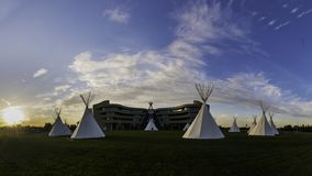 Native American Tepees on the Prairies at Sunset. An array of indigenous tee-pees on the prairie grass set up for a cultural event at sunset at Canada`s First stock photo