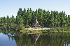 Native American tipi on a lakeshore. Traditional Native American tipi on a lakeshore royalty free stock image