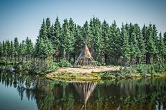 Native American tipi reflecting in the lake royalty free stock images