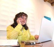 Native American woman on a cell phone in office. Native American woman talking on a cell phone while looking at something on the computer in her office Stock Photos