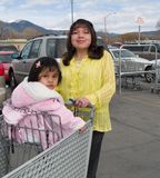 Native American woman heading to a grocery store. With her little daughter in a shopping cart Stock Photography