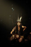Native American Woman on Her Knees Holding Wooden Stick Smiling Stock Images
