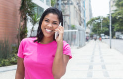 Native american woman laughing at phone in the city. With modern buildings in the background Royalty Free Stock Image