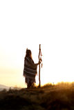 Native american woman  shaman with pikestaff on background of su. Nset beutiful in mountains Royalty Free Stock Photos