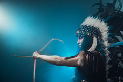 Native American woman shooting a bow Royalty Free Stock Image