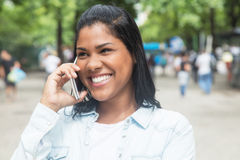 Native american woman speaking at phone in a park. With people in the background Stock Photography