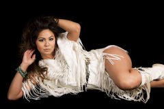 Native American woman in white outfit lay on black hand in hair. A Native American woman laying with a sensual expression on her face Stock Photography