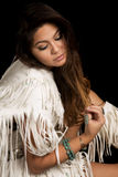 Native American woman in white outfit sit on black close look do. A Native American woman thinking and looking down Royalty Free Stock Image