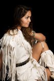 Native American woman in white outfit sit on black close look to. A Native American woman looking to the side, in her Native clothing Stock Image