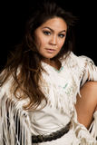 Native American woman in white outfit sit on black close looking. A Native American woman looking in her traditional outfit Stock Image