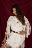Native American woman in white on red leg showing looking. A Native American woman in her Native dress looking Royalty Free Stock Photography