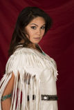 Native American woman in white on red side looking. A Native American woman in her traditional dress, looking over her shoulder Royalty Free Stock Photo