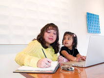 Native American woman at work with child. Native American woman working on a laptop while taking care of her daughter Royalty Free Stock Photos