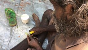 Native Australian Aboriginal man making a paint brush