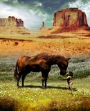 Native baby and horse. Native baby carressing the snout of a hourse in the middle of a field in Monument Valley Utah Stock Image