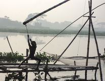 Native Bangladeshi poor kid. Trying to pull out the fishing net from water in Dhaka, Bangladesh Royalty Free Stock Images