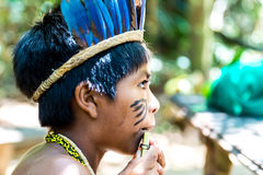 Native Brazilian boy playing wooden flute at an indigenous tribe in the Amazon.  Royalty Free Stock Photo