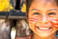 Native Brazilian girl smiling at an indigenous tribe in the Amazon.  Royalty Free Stock Images